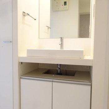 洗面台はスクエアでスタイリッシュ。大きな鏡がうれしい!(※写真は反転間取りの9階・清掃前のお部屋です。)