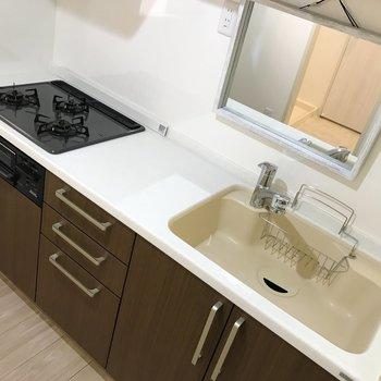 3口ガスコンロの付いたキッチンには鏡も。