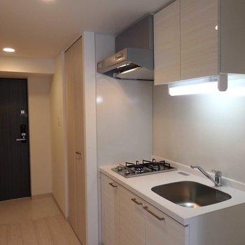キッチンは廊下に。2口コンロです。(※写真は13階の反転間取り別部屋のものです)