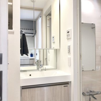 大きな鏡が付いた洗面台。※写真はモデルルーム・6階の同間取り別部屋のものです