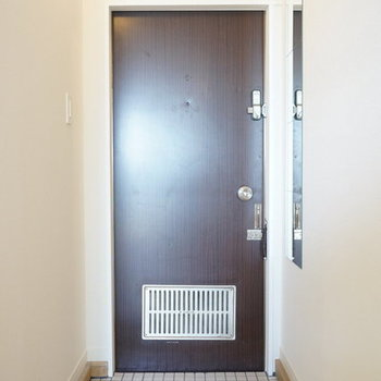 玄関には白いタイルに全身鏡で好印象(※前回工事の305号室です)
