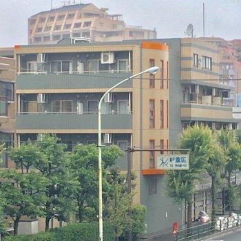 環八通り沿いに建つグリーン×オレンジのマンションです