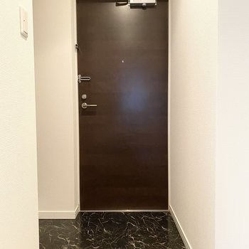 玄関のドアはシックな装いです。大理石調の床が◎