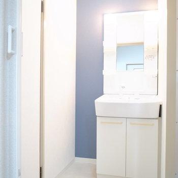 脱衣所のクロスは明るめのネイビー。洗面台のとなりには棚が置けそう。