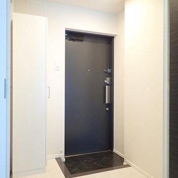 玄関は色と段差でセパレート。※写真は9階の同間取り別部屋のものです