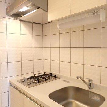 キッチンは2口コンロ。※写真は14階の同間取り別部屋のものです。