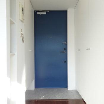 玄関はこちら。扉の青がいい感じ。※写真は9階の同間取り別部屋のものです