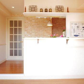 キッチンから見えるライトとレンガ調のクロスが素敵!