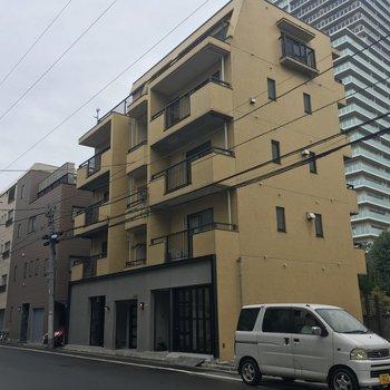 川沿いに立つシンプルなマンション。1階に注目!