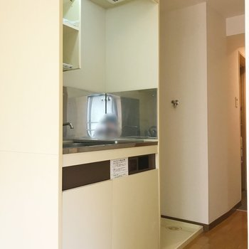 収納棚付きキッチン。奥は洗濯機置場です。