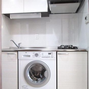 キッチンと洗濯機がセットになっています。※写真は6階の反転間取り別部屋、モデルルームのものです