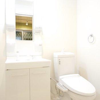 ウォシュレット付きのトイレと、 棚付きで使いやすそうな洗面台。