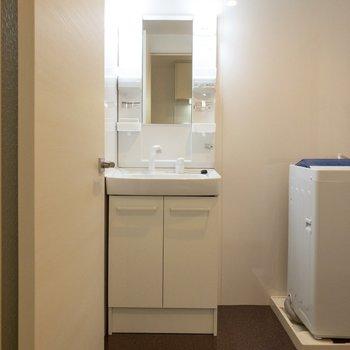 収納豊富な洗面台の隣には洗濯機置場。※写真は2階の同間取り別部屋のものです