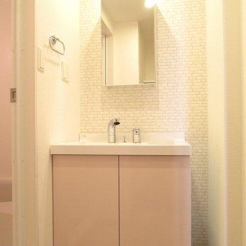 レンガ調の壁とピンクの洗面台は可愛いですね♫