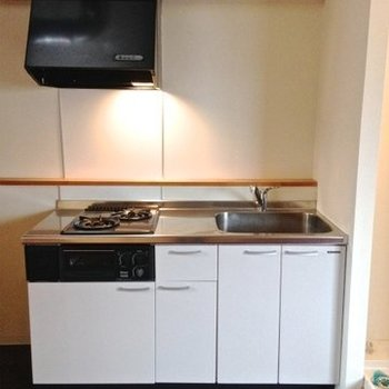 2口コンロのシステムキッチン。右には洗濯機置き場。※写真は6階の反転間取り別部屋のものです