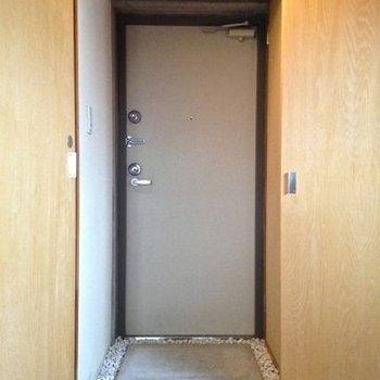 玉砂利が敷き詰められた玄関。靴箱も右手に。※写真は6階の反転間取り別部屋のものです