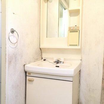 洗面台にはタオル掛けが横についていますよ※写真は2階の同間取り角部屋、清掃前のものです