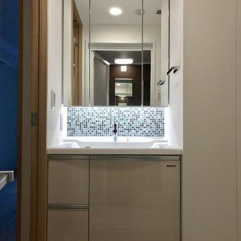 洗面台のタイルを照らす照明がいい仕事をしています。※写真と文章は2階の同間取り別部屋のものです