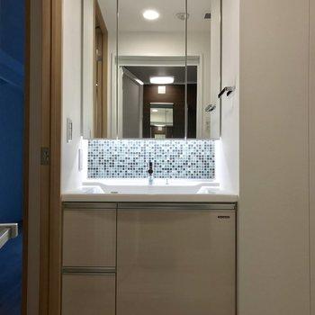 洗面台のタイルを照らす照明がいい仕事をしています。