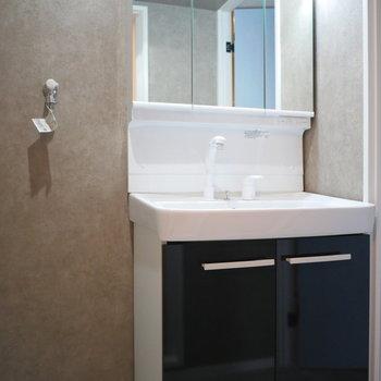 独立洗面台。脱衣室の壁紙がいい雰囲気