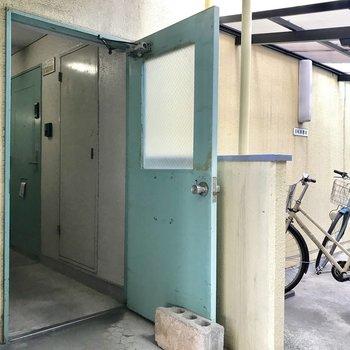 駐輪場隣の扉が入り口。駐輪場は屋根付きなのが嬉しい!
