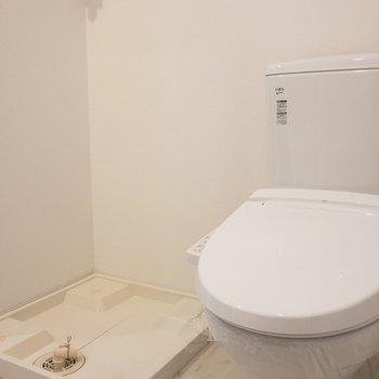 向かいのトイレと洗濯パン。※写真は7階の同間取り別部屋のものです