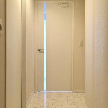 玄関前に水回りは集合しています。右側にトイレ、左側にサニタリーです。(※写真は20階の同間取り別部屋、モデルルームのものです)
