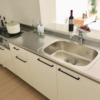 キッチンの作業スペースはシンクの両側に!コンロは2口です。※写真は2階の同間取り別部屋、モデルルームのものです