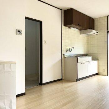 キッチンは白とブラウンの可愛い配色。すぐ隣には水回り。