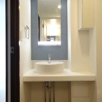 洗面台にも青いクロス!※写真は5階の反転間取り別部屋のものです