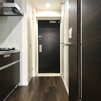 続いて廊下へ。ダークブラウンのキッチンがシックな印象。※写真は2階の同間取り別部屋のものです