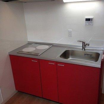 赤がおしゃれなシステムキッチン※写真は2階の同間取り別部屋のものです。