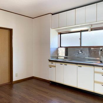 【DK】さて、両洋室から出ると。キッチンです。左の扉が玄関前の廊下に続いてます。