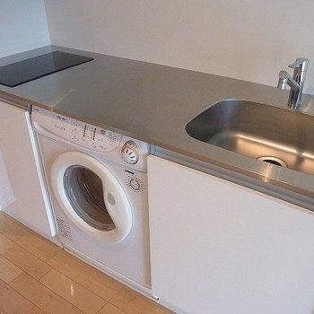 キッチンにはドラム式洗濯機付き。※写真は7階の同間取り別部屋のものです