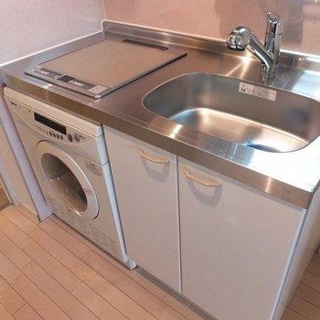 キッチンはコンパクト。ビルトイン洗濯機が設置されています。※写真は26階の同間取り別部屋のものです