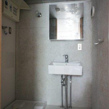 小さな洗面台と洗濯機置き場は隣り合わせ。