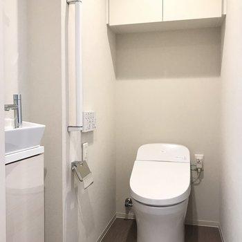 ウォシュレット付きトイレ。小さな洗面台も※写真は18階の反転間取り別部屋のものです