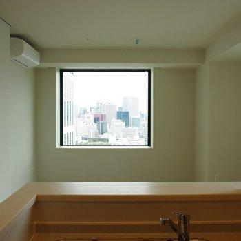 対面式キッチンから、お皿を手渡す※写真は18階の反転間取り別部屋のものです