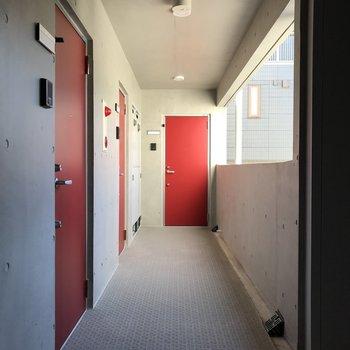 共用部。扉の赤がアクセント。