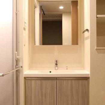 洗面台はシックなデザイン。※写真は9階の同間取り別部屋のものです