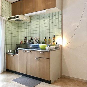 キッチンの淡いグリーンのタイルがアクセント。冷蔵庫にもこだわりたい(※写真の小物は見本です)