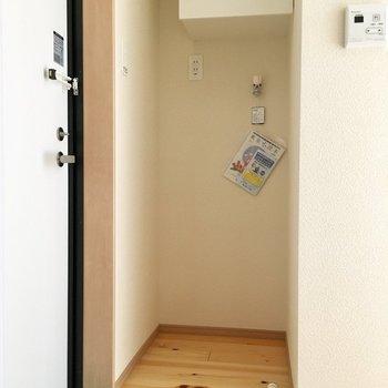 玄関横に、洗濯機置場。上部に収納も。
