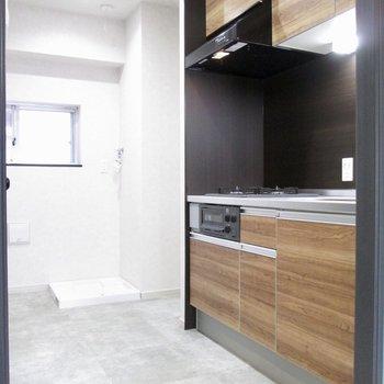キッチンは木目調に。奥は冷蔵庫置き場です。