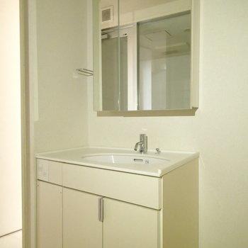 洗面台はこちら。横に洗濯機置場があります。 ※写真は1階の反転間取り別部屋のものです。