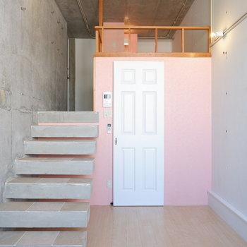 ピンクのアクセントクロスにコンクリート壁。