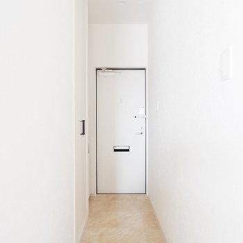 玄関へ。白い戸と壁がすっきりと。※写真は1階の同間取り別部屋、通電前のものです