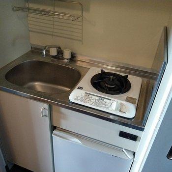 キッチンはコンパクトサイズ。コンロ下にミニ冷蔵庫が!