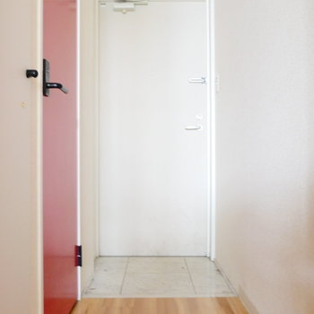 開くと玄関。赤扉がトイレです。 ※写真はクリーニング前・1階の同間取り別部屋のものです