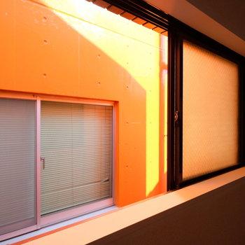 小窓のお隣はなんとオレンジの壁!オレンジ色の光が居室に反射して注ぎ込まれていました。