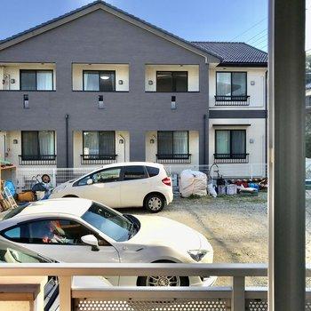 こちらはお隣の駐車場とお家がちらり。レースのカーテンがあるといいかな